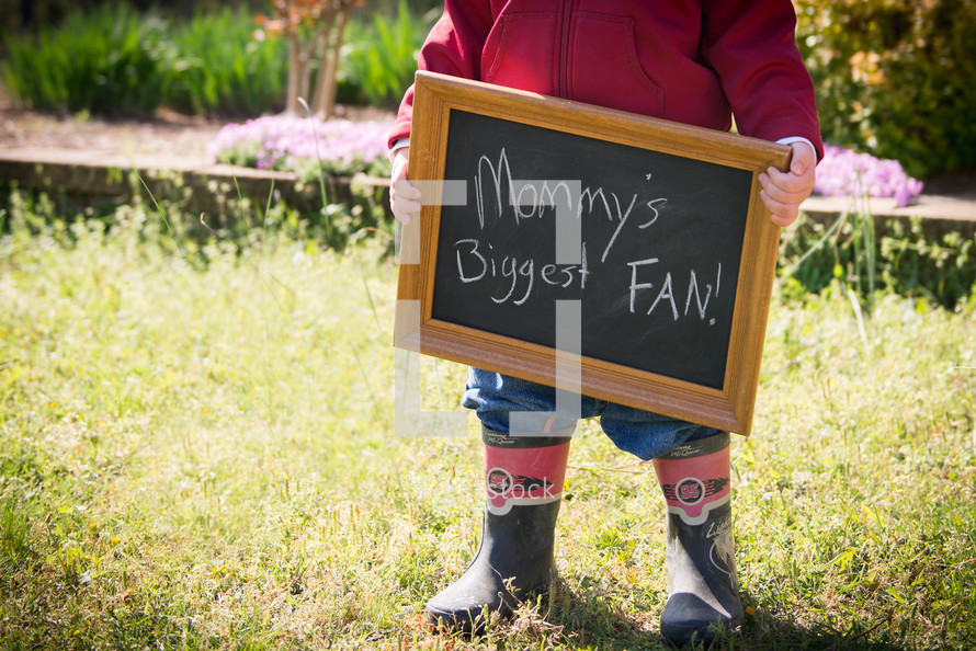 toddler boy holding a chalkboard sign that reads mommy's biggest fan