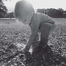 a toddler boy playing in gravel