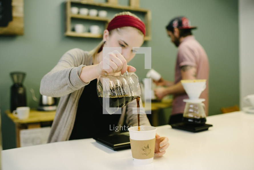 barista brewing coffee behind the counter