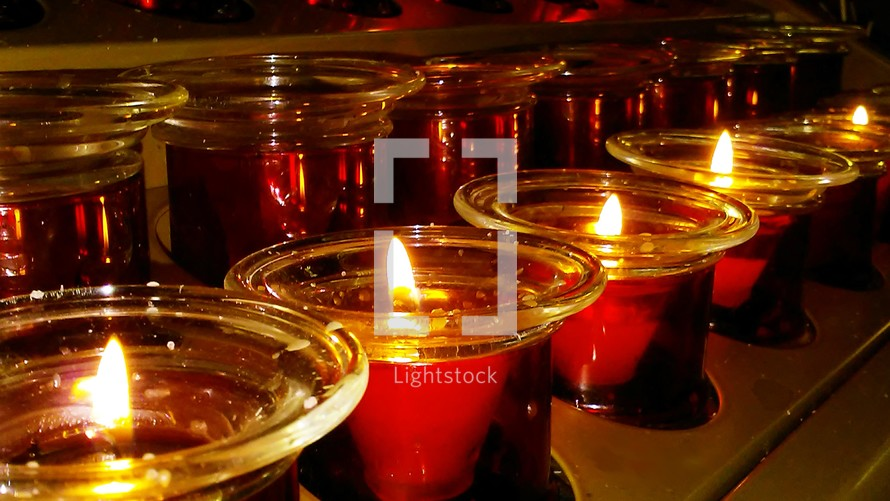 A row of red Christmas Candles lite for a Christmas Even Service or Prayer vigil candlelight service during church worship in an evening worship service at a local church during the holidays.