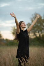woman in a field with her hands raised in praise and worship to God
