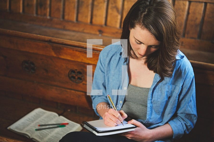 a woman writing in a notebook while sitting in a church pew