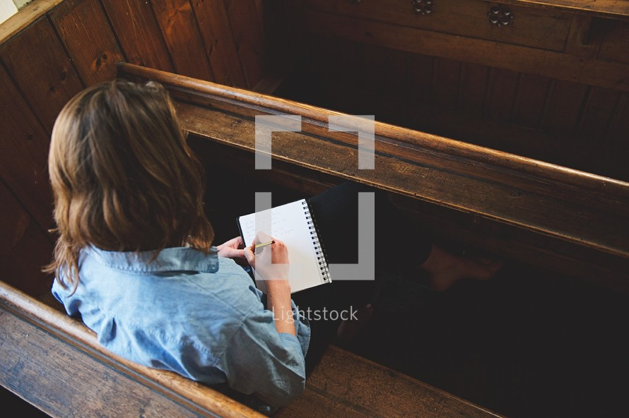 a woman sitting in a pew writing in a notebook