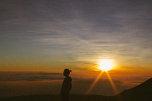 side profile silhouette of a man standing on a mountaintop at sunrise