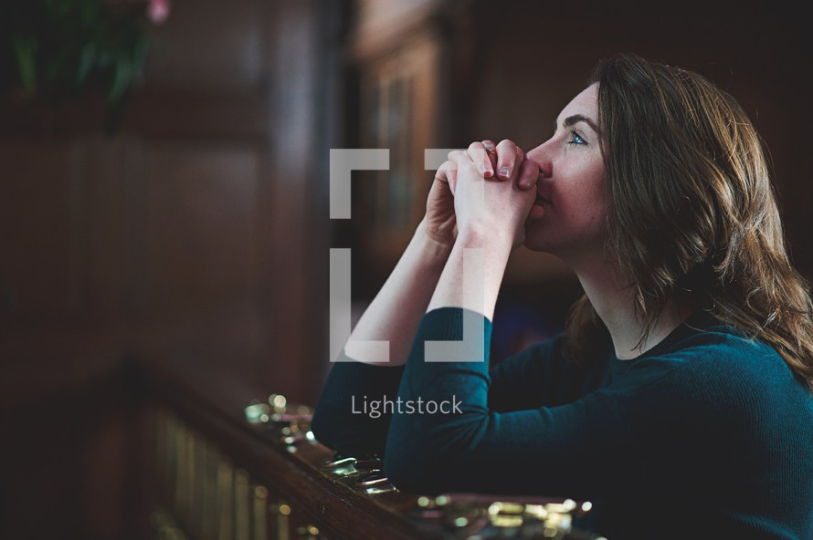 a woman on her knees praying at the altar