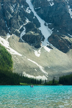 avalanche on a mountain side and canoe on a mountain lake