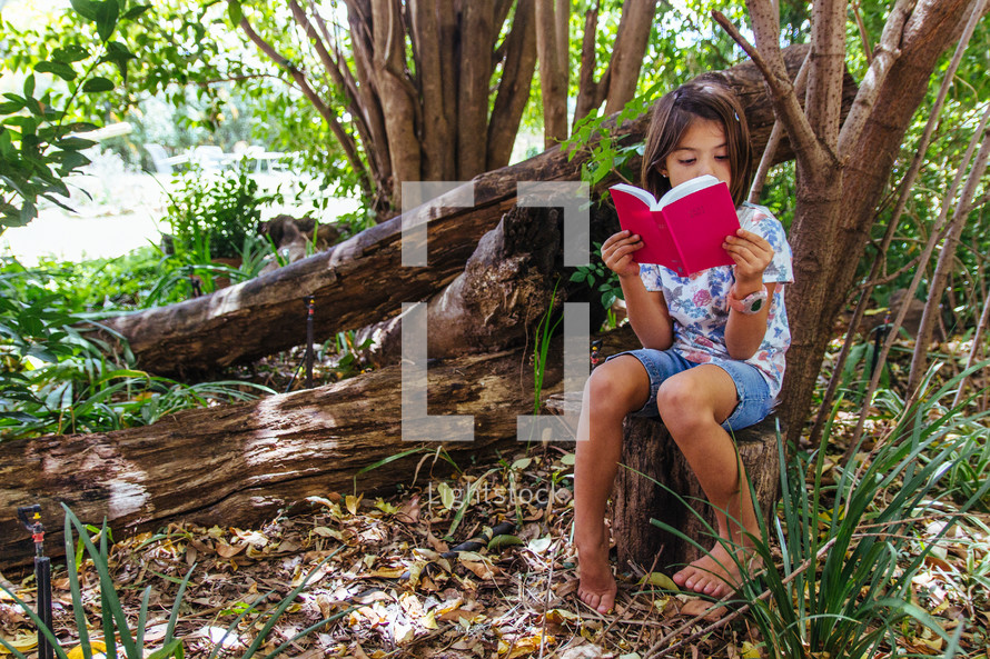 girl child reading outdoors