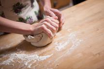 a woman kneading dough