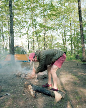a with an ax chopping up firewood