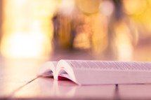 bokeh sunlight and open Bible on a wood floor