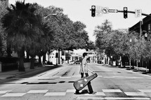 A man with a guitar crossing an intersection.