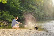 Boy with dog skipping rocks on river