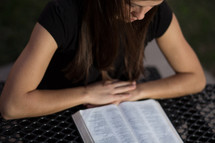 Woman reading Bible outdoors