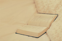 An open Bible laying on a bed.