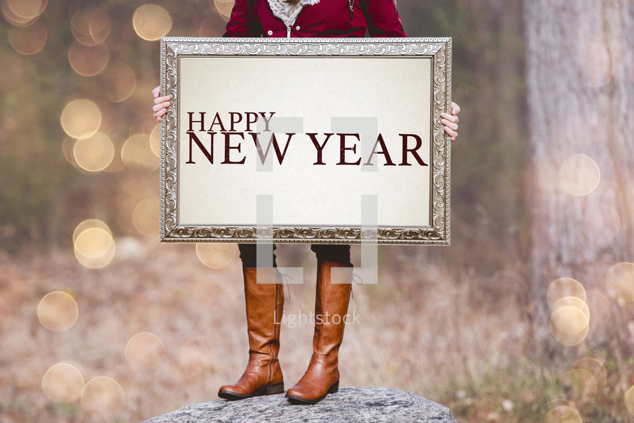 a woman holding a sign the reads Happy New Year