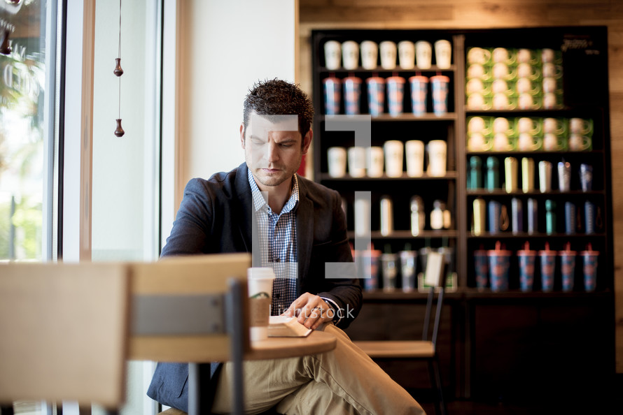 man reading a Bible in a coffee shop