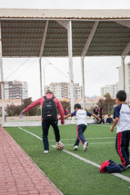 kids on a soccer field with their coach in La Serena, Chile
