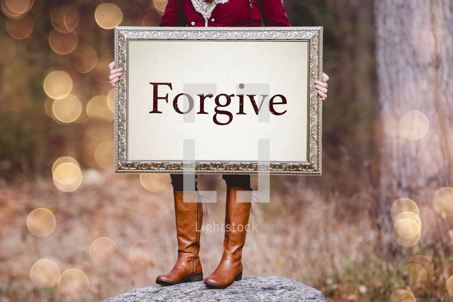 woman holding a frame with the word forgive
