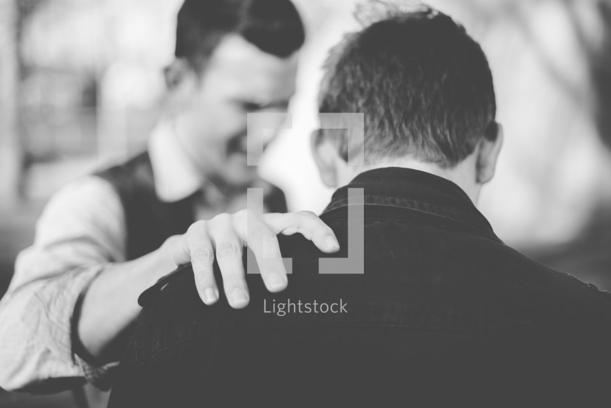 man praying over another