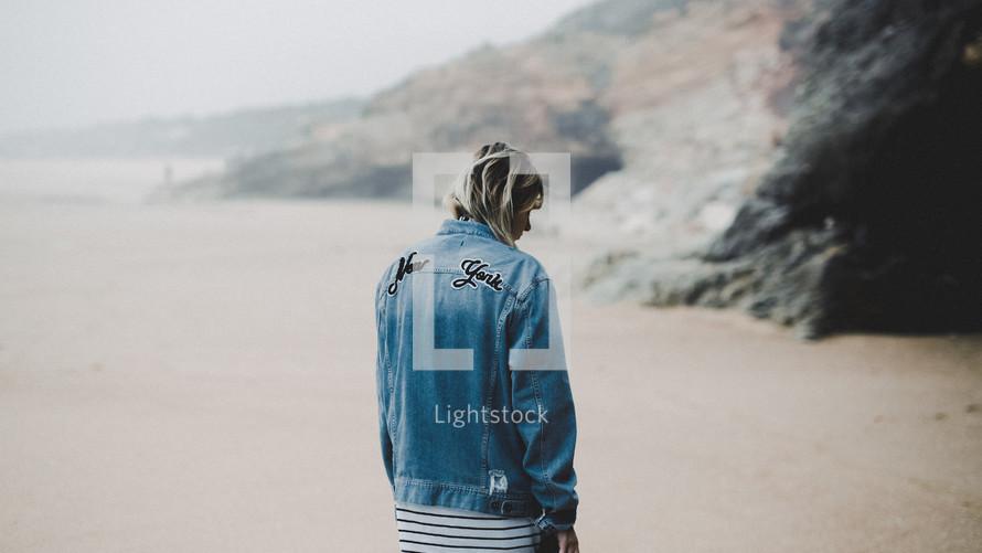 a woman in a denim jacket walking on the beach