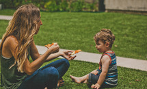 mother and son eating pizza, having a picnic in the grass