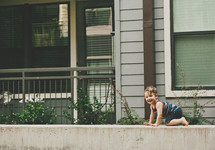 toddler boy crawling on a concrete wall
