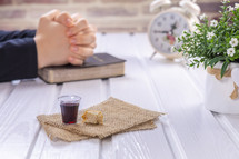 praying hands and communion elements