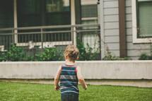 a toddler boy running in the grass