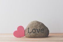 a rock with the word with the word love and a red heart