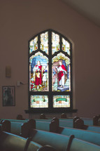 pews in a church and stained glass window of Jesus
