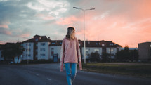 a woman walking down a street at sunset