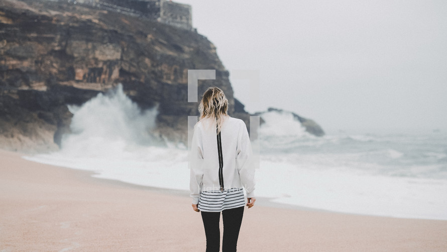 woman standing on a beach and waves crashing into rocks