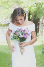 a smiling bride holding a bouquet of flowers