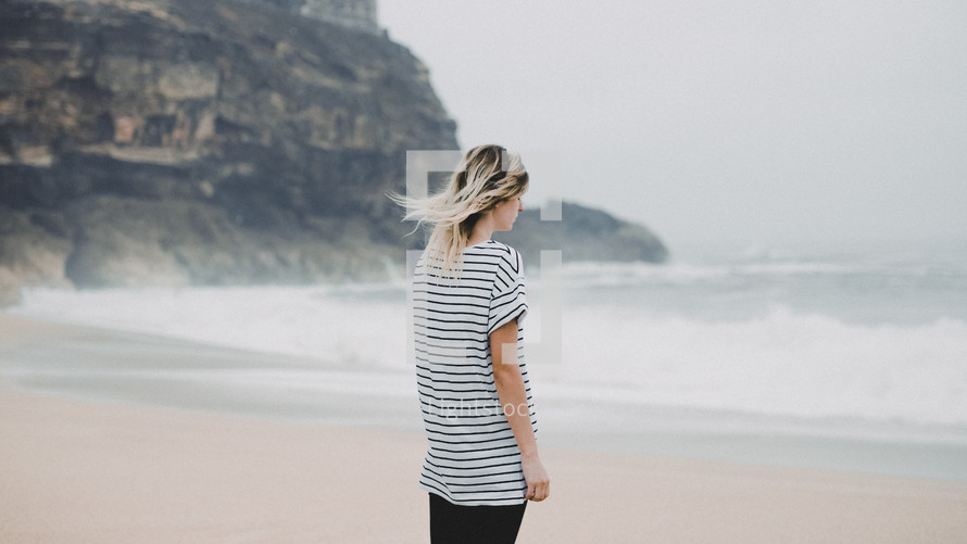a woman in a striped shirt standing on a beach