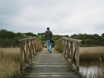 man crossing over a footbridge over a marsh