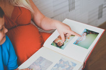 a pregnant mother looking a baby pictures of her son in a photo album
