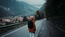 a woman in rain gear backpacking down a road