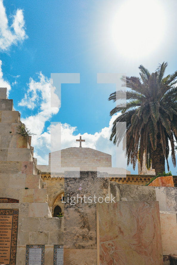 palm tree and cross on a historic stone church