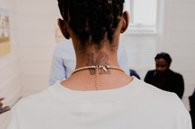 necklace on a love tattoo on a neck