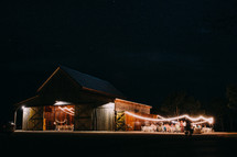 An old barn lit by strings of lights for a party.