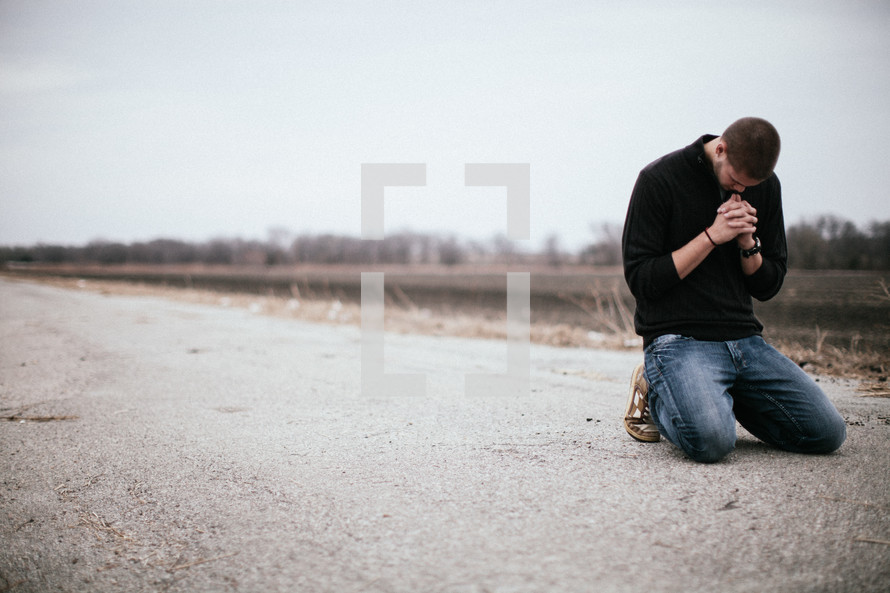 man kneeling in prayer in the middle of a road