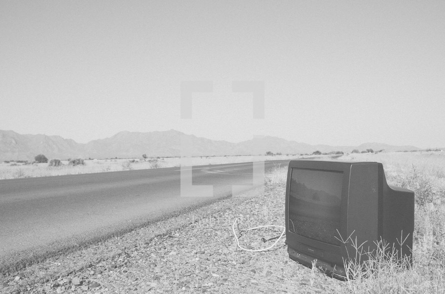 abandoned television on the side of a road
