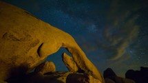 Timelapse of Milky Way galaxy stars rising over Arch Rock with clouds rolling by in the night sky.   This time-lapse was filmed in Joshua Tree National Park.