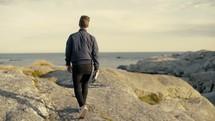 man walking on a rocky shore carrying a Bible
