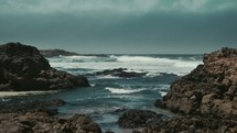 Ocean waves crashing onto the rocks on shore.