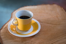 coffee cup and saucer on a cut log table