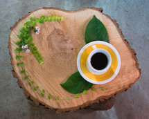 cut wood table, coffee cup and saucer, and leaves