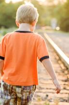 a boy child walking on railroad tracks