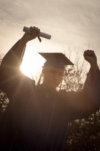 a graduate holding up his diploma