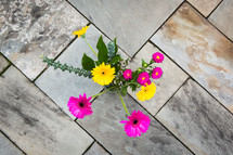 looking down at flowers in a vase on a tile floor